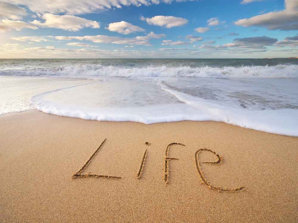 the word life being washed away in the sand