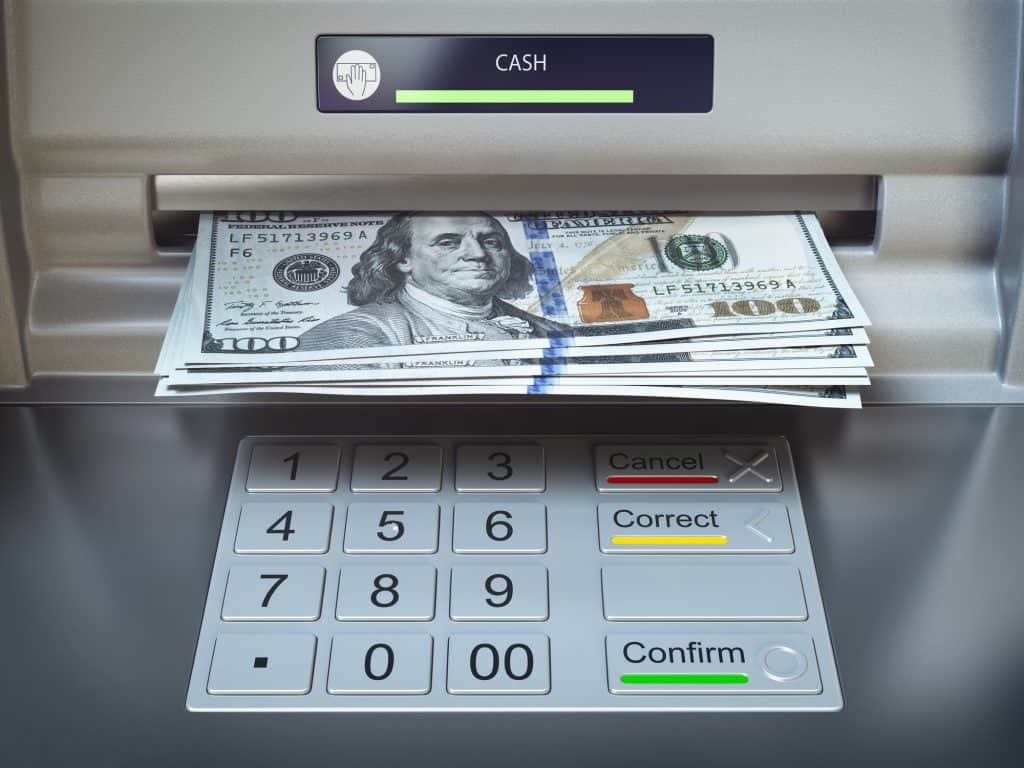 ATM machine and money. Withdrawing dollar banknotes.