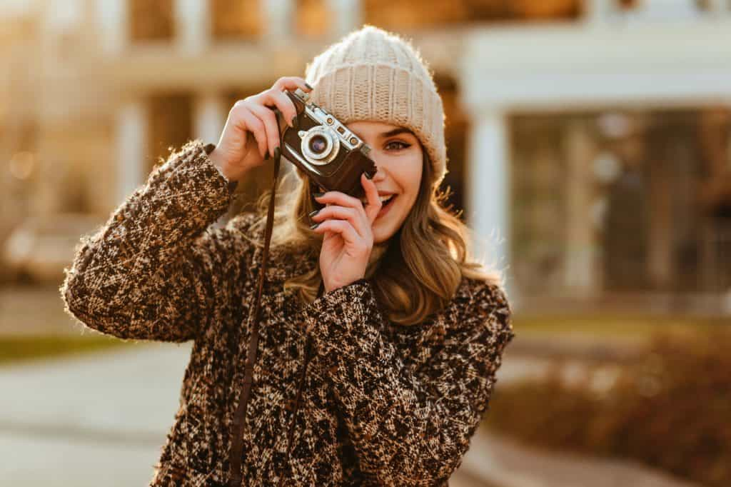 Blissful female model in elegant coat posing with camera. Smiling photographer taking pictures of a