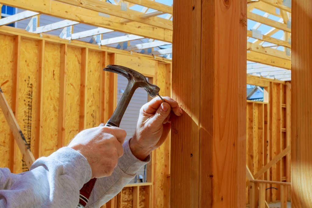 builder hammers a nail into a wooden beam New building home, nailing hammer