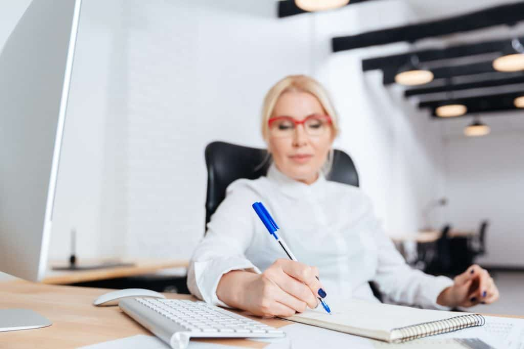 Businesswoman writing in notebook in office