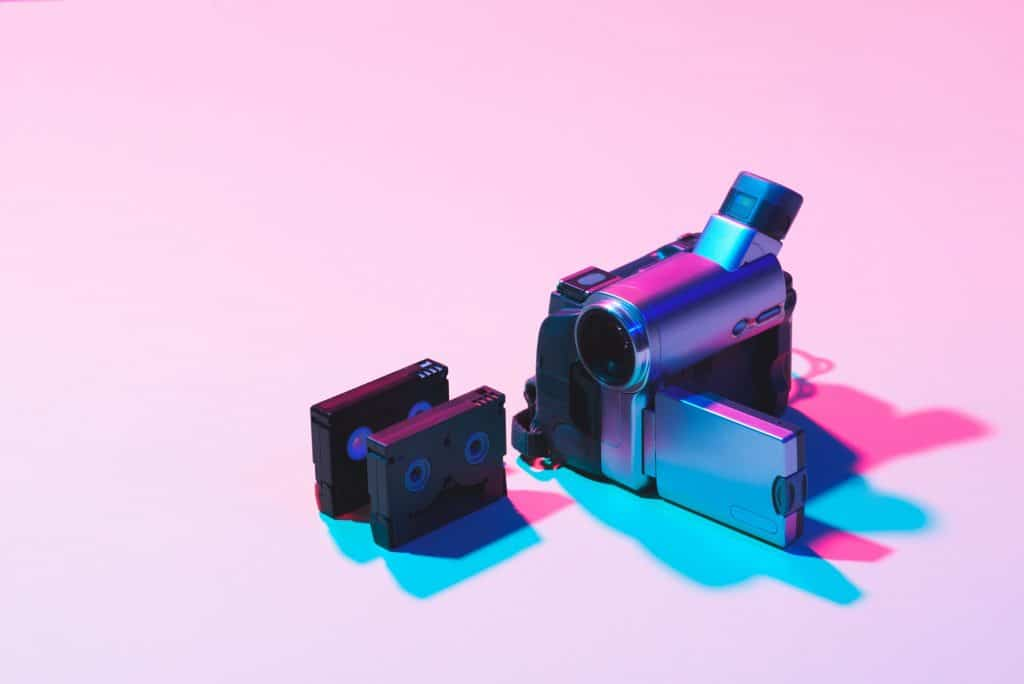 close up view of arranged video cassettes and digital video camera on pink background