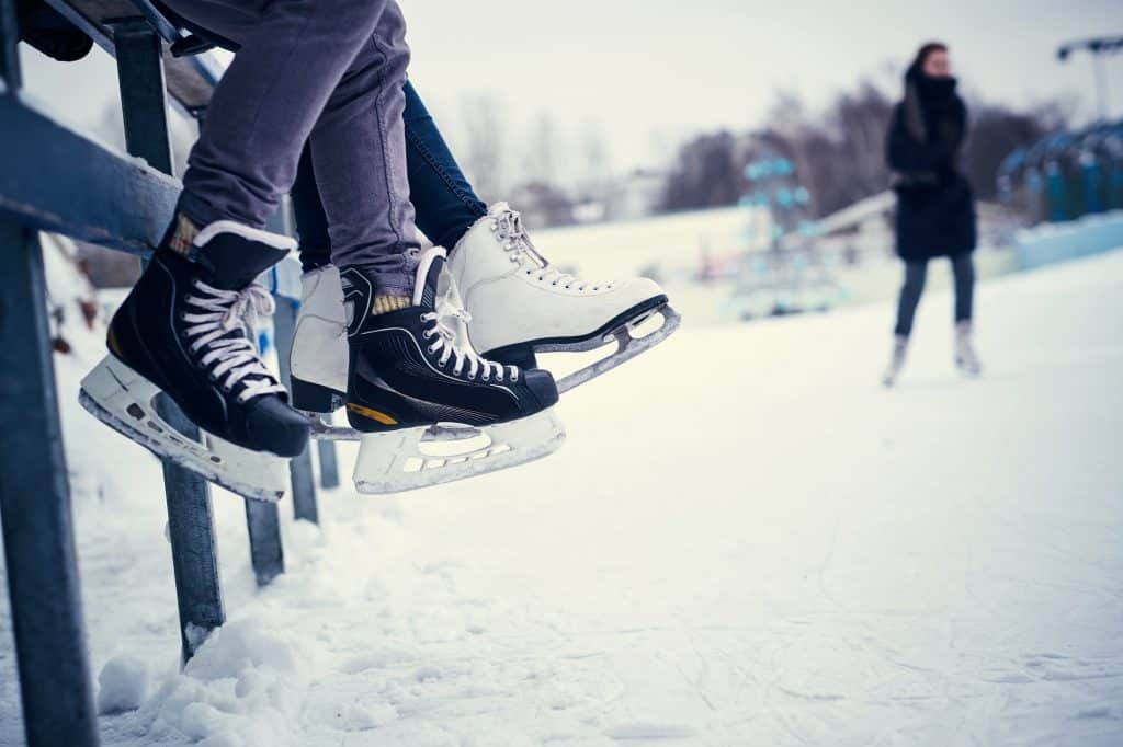 Couple wearing ice skates sitting on a guardrail