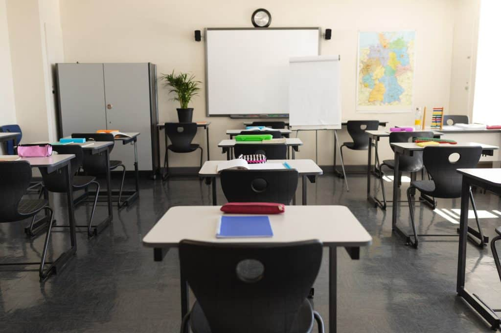 Empty classroom with desk and whiteboard in school