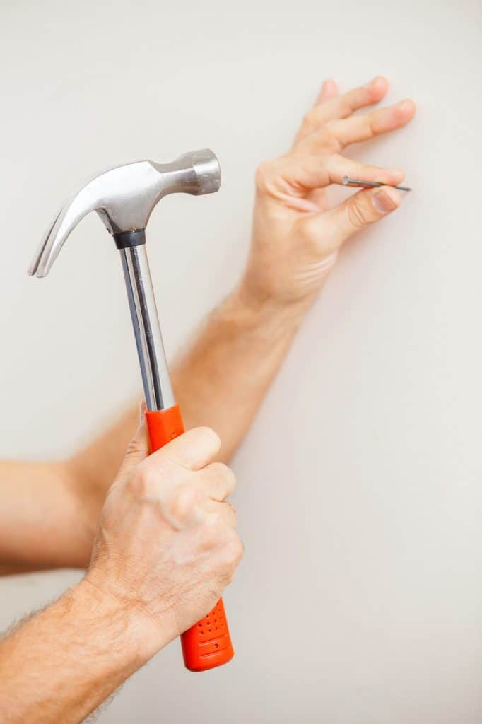Hammering a nail. Close-up of man hammering a nail