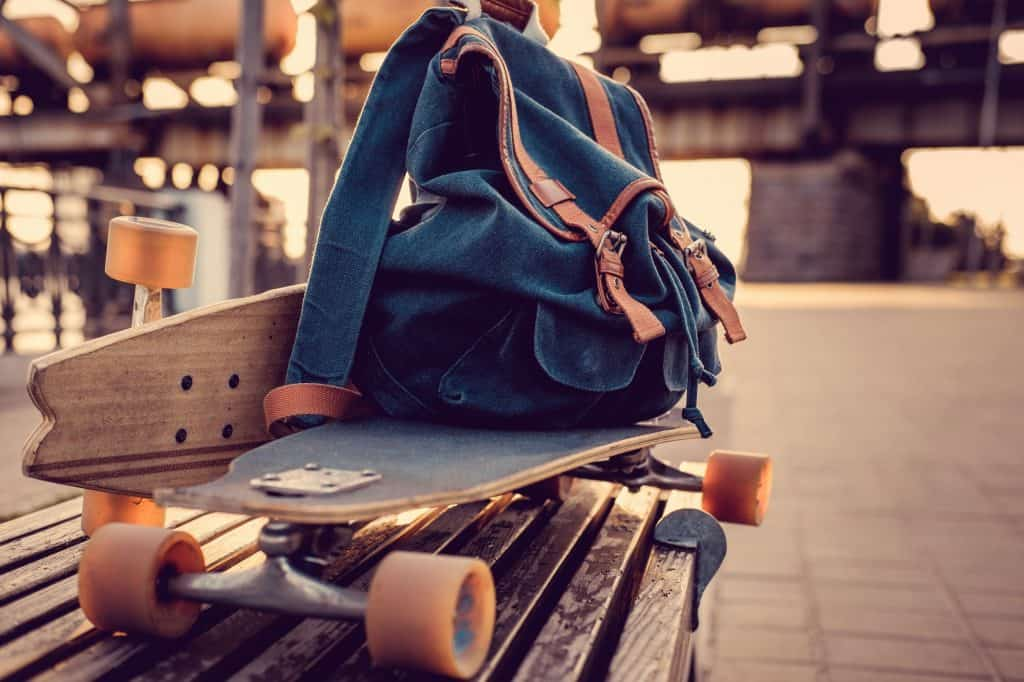 Longboard and backpack on a bench.