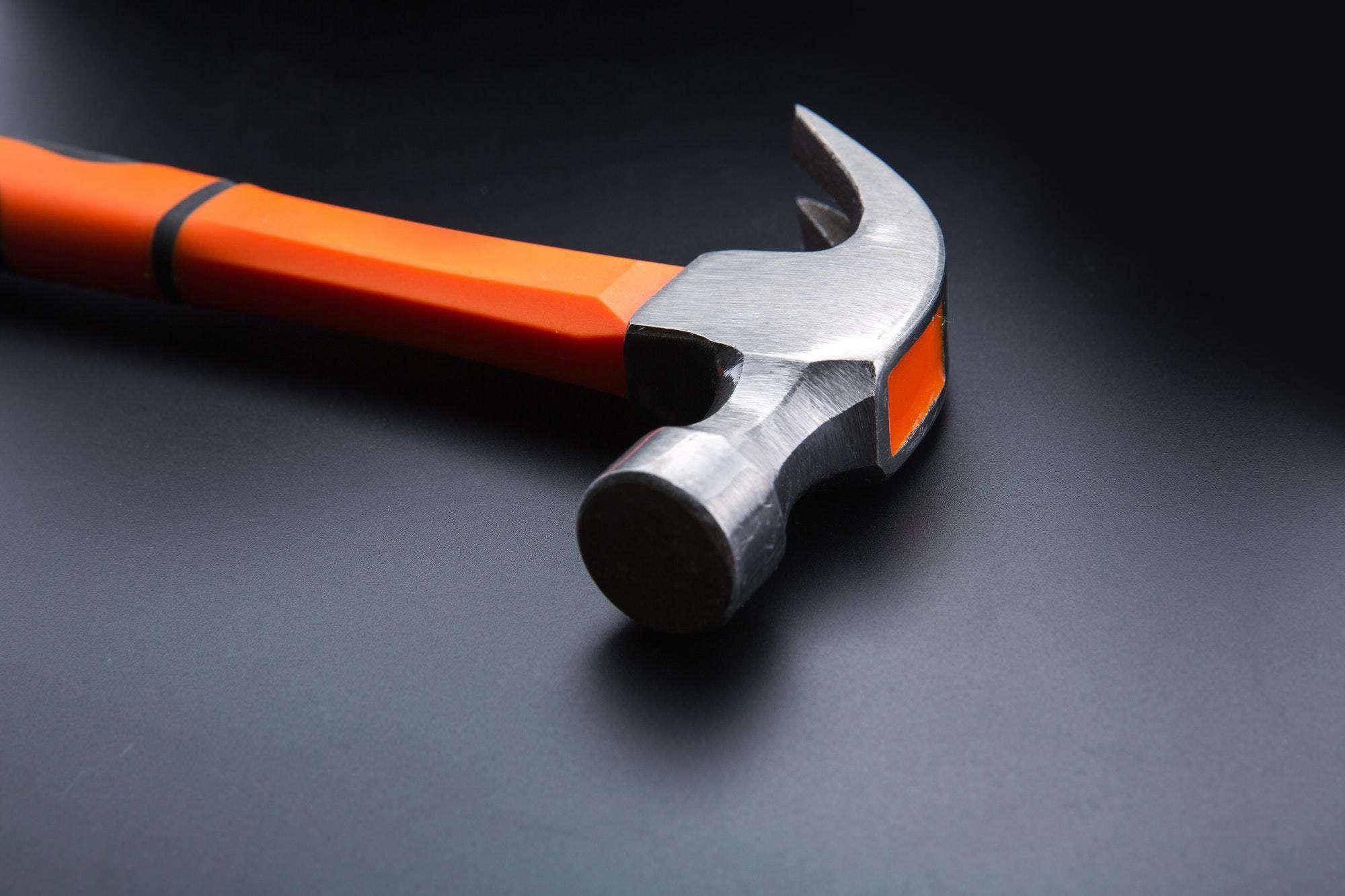 Orange hammer on dark matt background, closeup