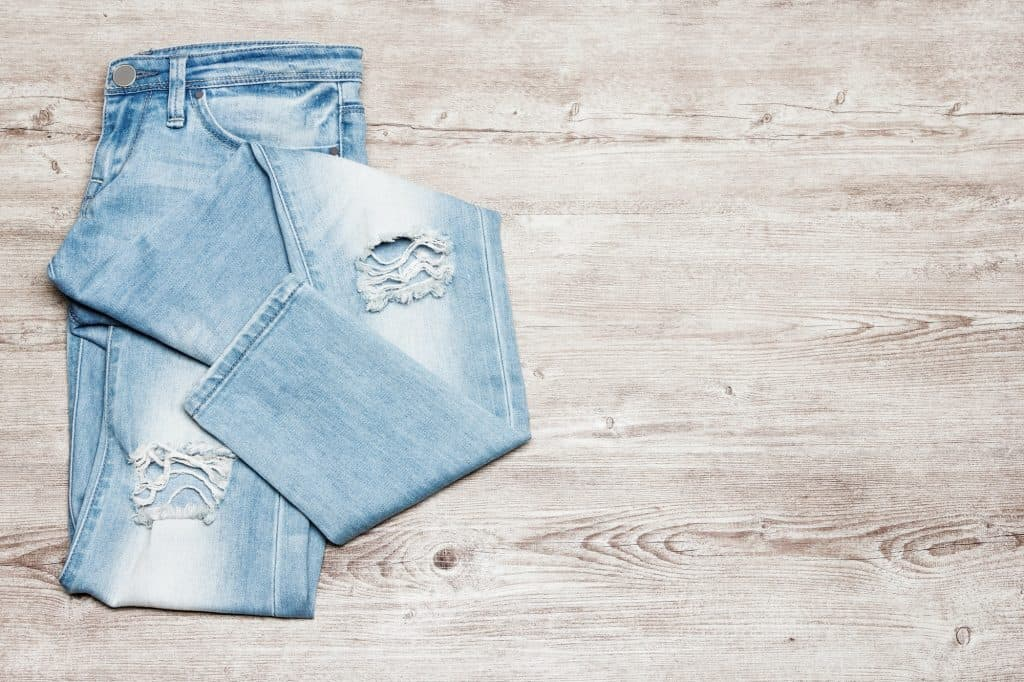 Ripped jeans on shabby wooden background with free space for tex